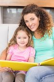 Pretty mother sitting with her little daughter reading a storybook at home in living room