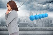 foto of newton  - Concentrating businesswoman against newtons cradle above city - JPG