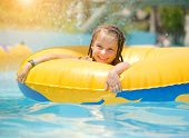 image of one piece swimsuit  - Cute little girl  sitting on inflatable ring in swimming pool - JPG