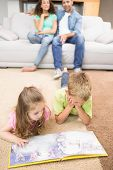 Happy siblings lying on the rug reading a storybook at home in living room