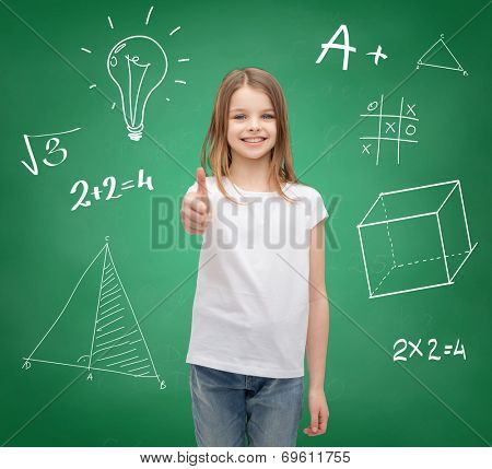 school, childhood, gesture and education concept - smiling little girl in white blank t-shirt showing thumbs up