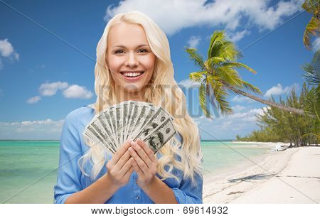 finances and people concept - smiling woman in red dress with us dollar money over tropical beach background