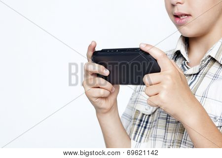 Closeup of teen boy playing video games in a portable game console against gray background