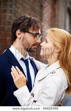 Portrait of amorous dates looking at one another outside