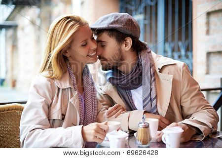 Portrait of affectionate couple in stylish clothes spending time in cafe