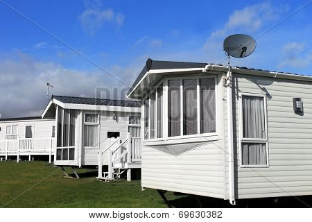 Scenic view of a caravan or trailer park in summer with blue sky and cloudscape background.