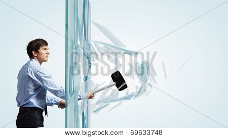Young determined businessman breaking glass with hammer