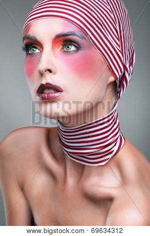 Portrait of girl with a bright theatrical make-up with the striped scarf on a head
