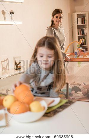 Little girl having breakfast, mother in the background on playpen
