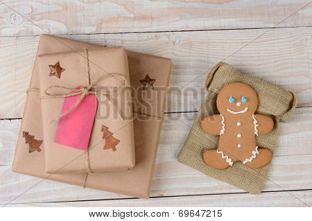 High angle shot of two Christmas presents and a gingerbread man on a whitewashed wood table. The cookie is on a burlap bag.