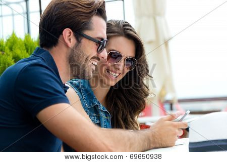 Happy Couple Of Tourist In Town Using Mobile Phone.