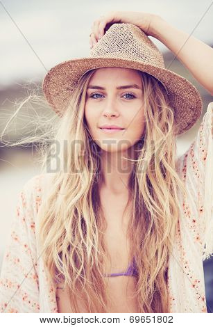 Portrait of a beautiful young girl in a hat. Warm vintage fashion color tones.