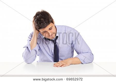 Disappointed young man sitting on a table, isolated on white background