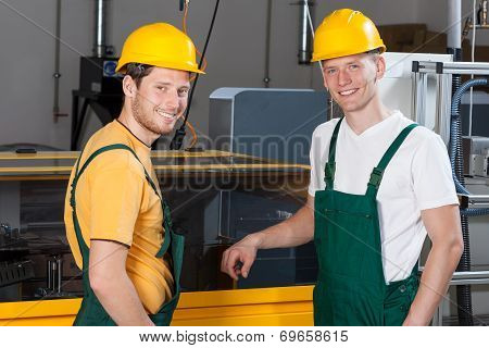 Workers Standing Next To Machine