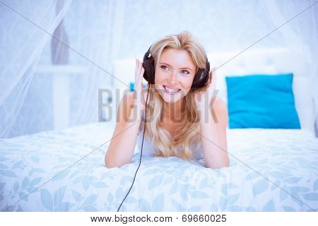Quiet woman enjoying some music in her bedroom wearing headphones