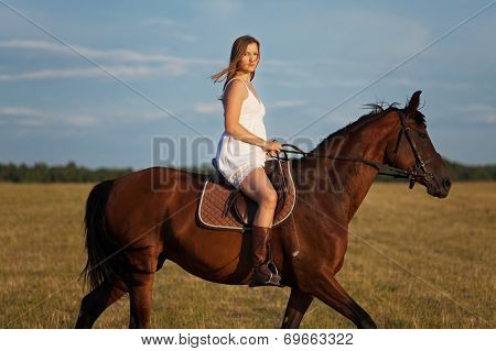 Woman In Dress Riding On A Brown Horse