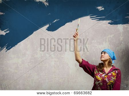 Young woman in headscarf painting wall with brush