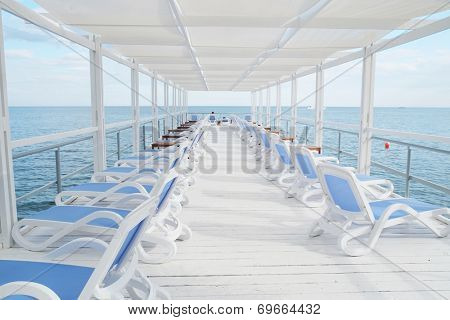 White plastic sunbeds in line