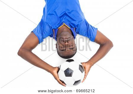 Football player lying on the ground holding ball with eyes closed on white background