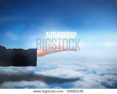 Businesswomans hand presenting the word authorship against blue sky over clouds at high altitude