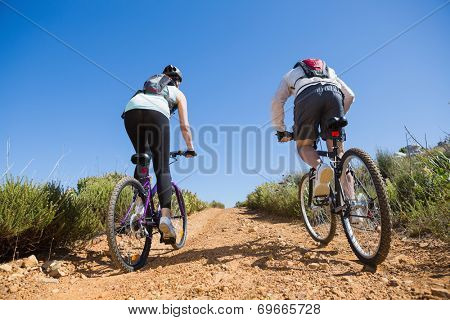 Active couple cycling uphill on a bike ride in the country on a sunny day
