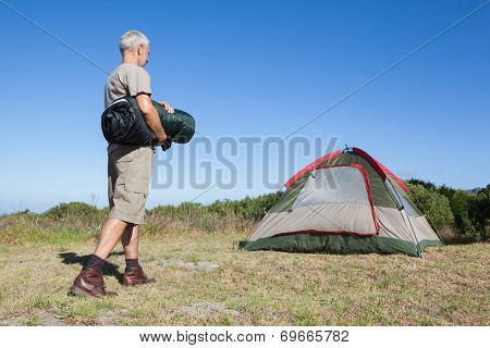 Happy camper walking towards his tent holding sleeping bag on a sunny day