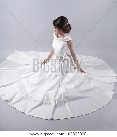 Beautiful Charming Bride In A Luxurious Dress Sitting Over Gray Background.