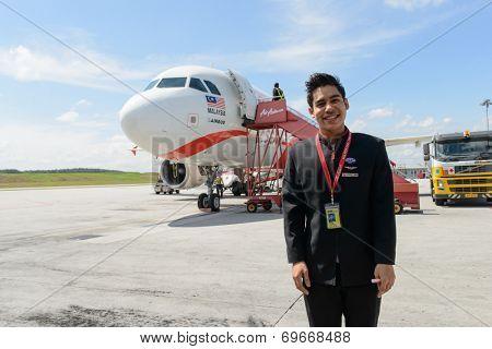 KUALA-LUMPUR - MAY 06: Airasia crew member on May 06, 2014 in Kuala-Lumpur, Malaysia. AirAsia Berhad is a Malaysian low-cost airline headquartered in Kuala Lumpur, Malaysia