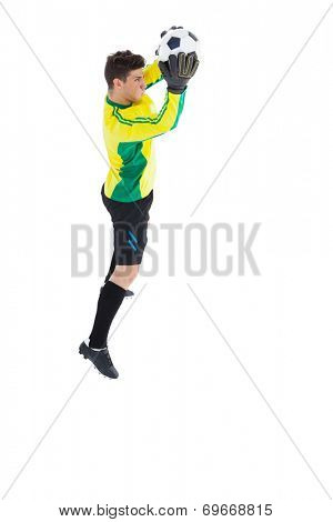 Goalkeeper in yellow making a save on white background