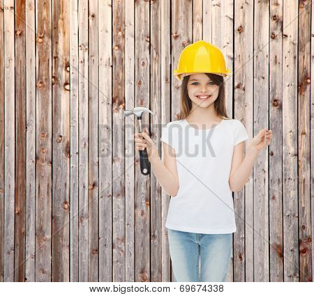 childhood, construction, architecture, building and people concept - smiling little girl in protective helmet with hammer