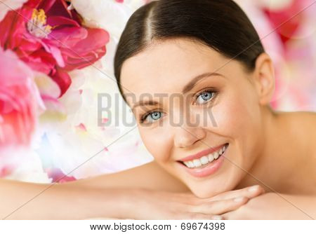 health and beauty, resort and relaxation concept - woman in spa salon lying on the massage desk