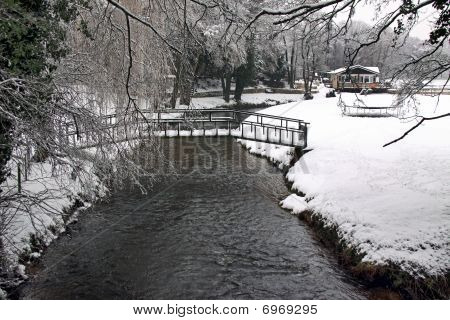 Remote house in winter snow with bridge, river and forest