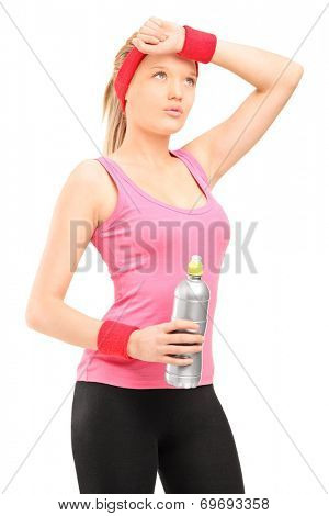 Exhausted athletic woman in sportswear holding a bottle of water isolated on white background
