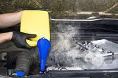 image of steam  - A mechanic pours engine coolant into an overheated automobile radiator in an attempt to cool it down and stop the steam - JPG