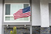 image of patriot  - American flag blowing in the breeze while hanging on a residential home symbolizes a patriotic holiday in the United States - JPG