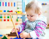 picture of playgroup  - cute little girl in the classroom early development plays with numerous bright toys - JPG