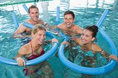 foto of day care center  - Happy fitness class doing aqua aerobics with foam rollers in swimming pool at the leisure centre - JPG