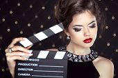 image of superstars  - Fashion woman with sexy red lips holding cinema clap - JPG