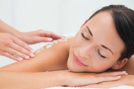stock photo of scrubs  - Peaceful brunette getting a salt scrub beauty treatment in the health spa - JPG
