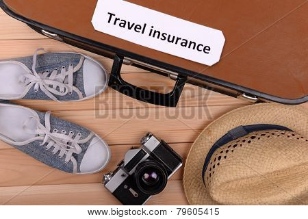 Suitcase and tourist stuff with inscription travel insurance on wooden background top view
