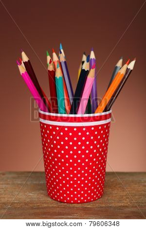 Colorful pencils in red plastic cup on wooden table and shaded color background
