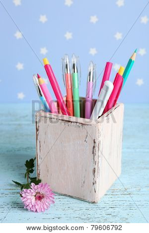 Holder with pens and pencils near flower on color wooden table on color wooden table and blue background with printed stars