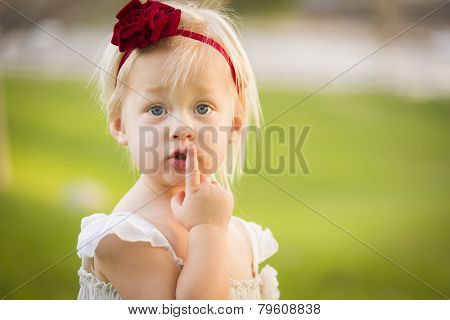 Beautiful Adorable Little Girl With Her Finger on Her Mouth Wearing White Dress In A Grass Field.
