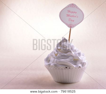 Delicious cupcake with inscription on table on beige background