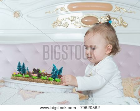 Small caucasian child girl on happy birthday with cake at home