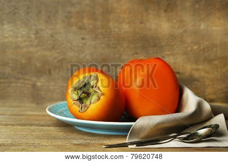 Ripe sweet persimmons, on wooden table