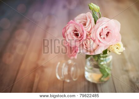 Colorful still life with roses in glass vase with bokeh background