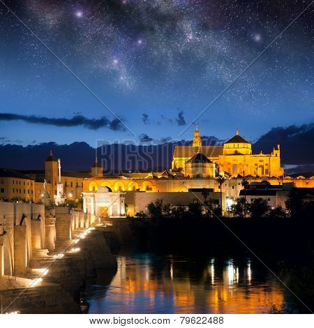 Cityscape of Cordoba at night with Roman bridge and Mezquita, Andalusia, Spain - sky with stars