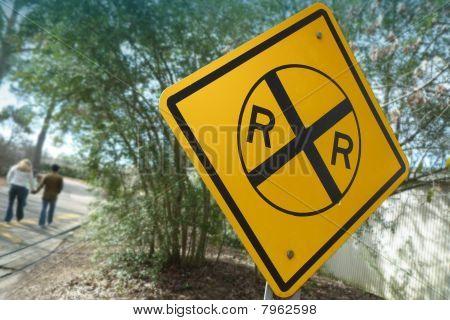 ein paar Holding hände an ein Railroad Kreuzung Zeichen
