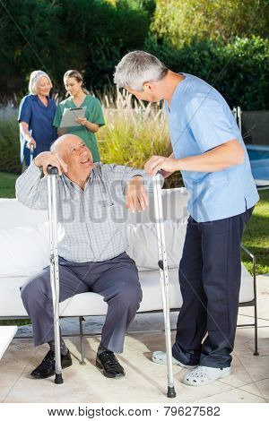 Male and female caretakers helping senior people in nursing home